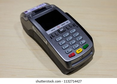 Credit Debit Card Reader Machine or Credit Debit Card Terminal on wooden table.