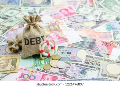 Credit default insurance / debt security concept : Debt bags, red lifebuoy on world banknotes e.g dollar, yuan, depicts a financial agreement that mitigates the risk of loss from default by a borrower