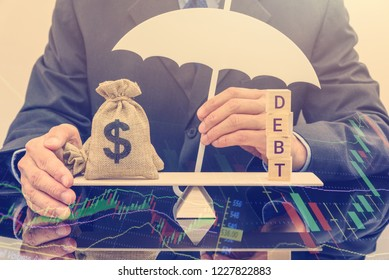 Credit default insurance / debt security concept : Businessman protects US dollar bag on a basic balance scale, depicts a financial agreement that mitigates the risk of loss from default by a borrower