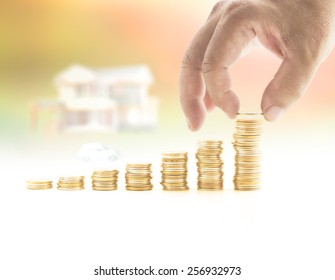 Credit money concept: Human hand adding a golden coin in stack of coins over blurred house and car on sunset background.