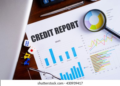 """""""Credit Report"""" text on paper sheet with magnifying glass on chart, dice, spectacles, pen, laptop and blue and yellow push pin on wooden table - business, banking, finance and investment concept"""