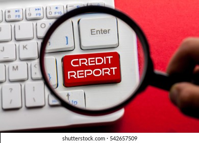 Credit Report word written on keyboard view with magnifier glass