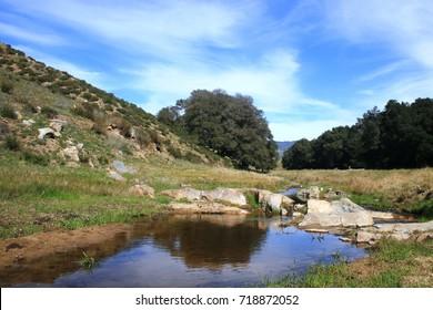 Creek below blue sky with clouds in rolling hills, California
