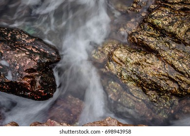 Creek or stream water flowing past rocks and stones