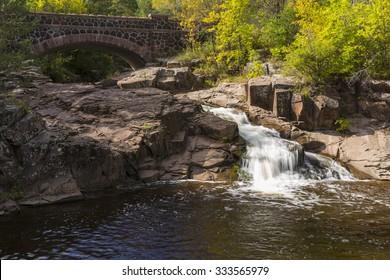 Creek Waterfall with Stone Arch Bridge