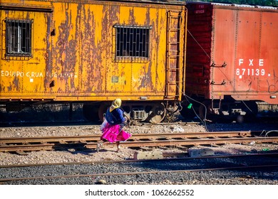 CREEL, MEXICO-Jan 2016: A native Raramuri woman in bright clothing runs across railway tracks while waiting for the El Chepe Copper Canyon train at Creel railway station in Chihuahua, northern Mexico