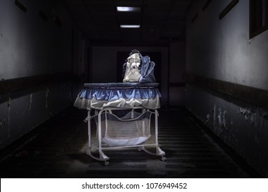 creepy baby bassinet placed directly under the still working light in an abandoned hospital