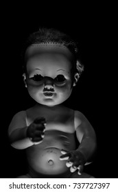 creepy baby doll sitting in the dark and high contrast concept