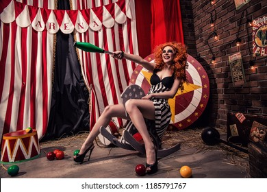 Creepy and beautiful female clown rides toy horse and points in laughter with skittle somewhere on scene of dark circus arena