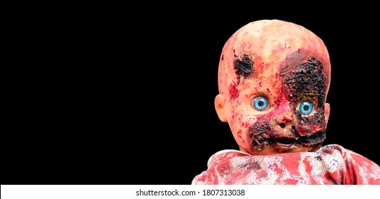 Creepy bloody doll Halloween concept, Close up of children Ghost mystic doll, Scary horror doll face isolated on black background.