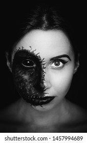 Creepy close-up portrait of a woman with black eye and a cursed mark on her face on dark background. Demonic nature in an innocent body