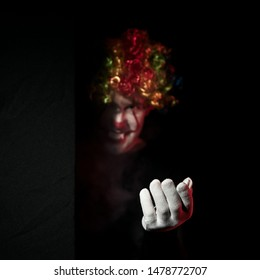 A creepy clown in a colored wig looks around the corner and beckons to himself with a gesture of his hand. Stands in a dark room and smiles.
