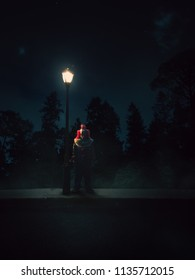 Creepy clown standing beside a lampost at night / high contrast image