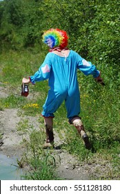 Creepy Clown Walking in the Woods With a Gun and a Bottle - Summer Scene