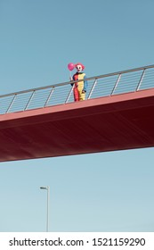 a creepy clown wearing a colorful yellow, red and blue costume, holding a red balloon in his hand, standing in a bridge outdoors