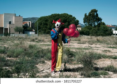 a creepy clown wearing a yellow, red and blue costume, holding a bunch of red balloons in his hand, standing in a vacant lot