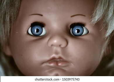 Creepy and dark doll's head. A scary face of a blonde baby vintage doll with blue eyes