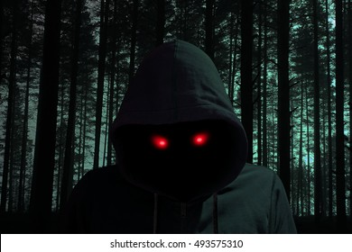 Creepy dark man with glowing red eyes in a black forest halloween concept