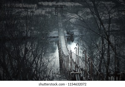 Creepy dark old suspension bridge across the river in the fog. Background for halloween.