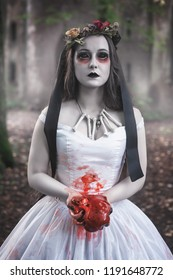 Creepy dead bride with bloody meat in hand. Halloween scene
