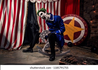 Creepy dead male soldier in blue uniform with long nails freaks out and rides toy horse in dark circus arena