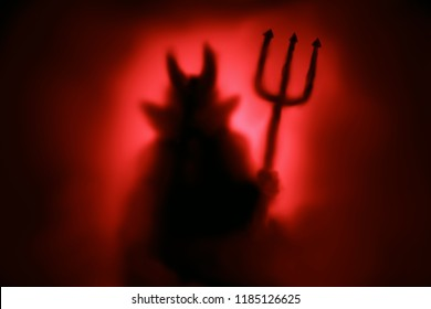 Creepy Devil silhouette from hell in the mist with backlit.