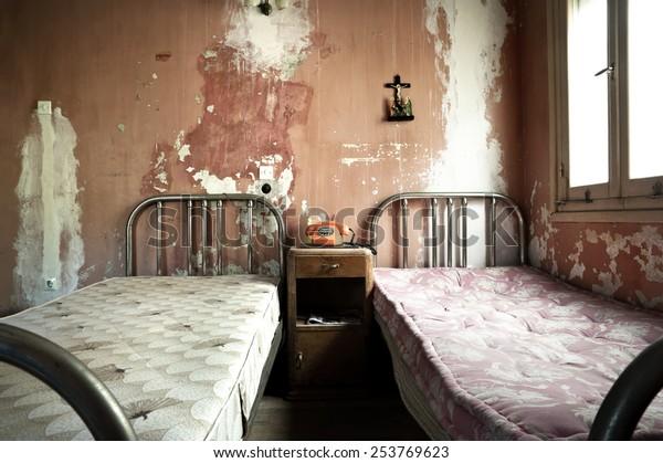 schmutziges und verlassenes Schlafzimmer mit gekrackten Wänden