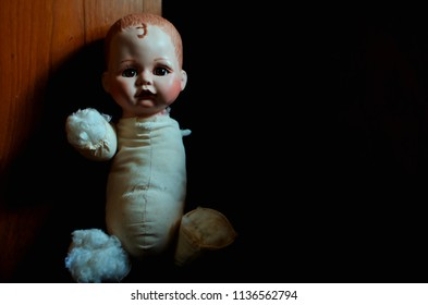 creepy disabled doll looking forward in the dark and high contrast concept