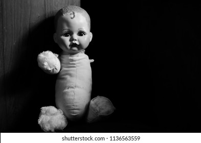 creepy disabled doll sit in the dark in black and white and high contrast concept