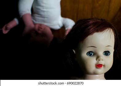creepy doll behind cute doll