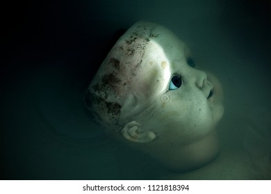 Creepy doll face in dark dirty water