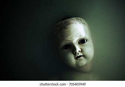 Creepy doll face in dark dirty water