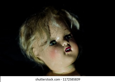 creepy doll head and black background in high contrast