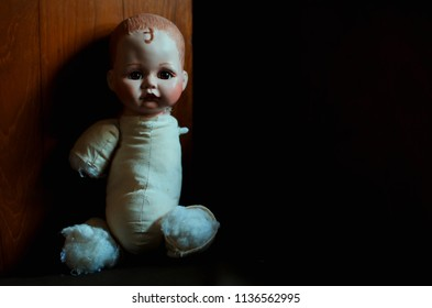 creepy doll looking forward in the dark and high contrast concept