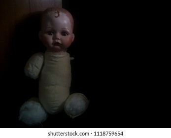 creepy doll looking forward and sit in the dark room in high contrast concept