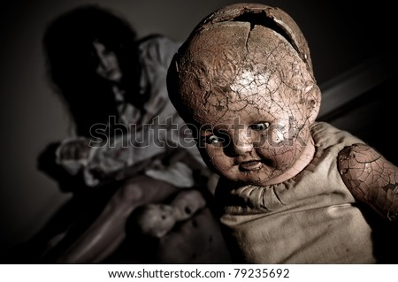 Creepy Doll with Possessed Woman holding doll parts in the background focus is on Doll