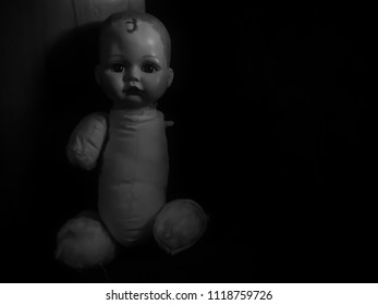 creepy doll sit in the dark room in black and white and high contrast concept
