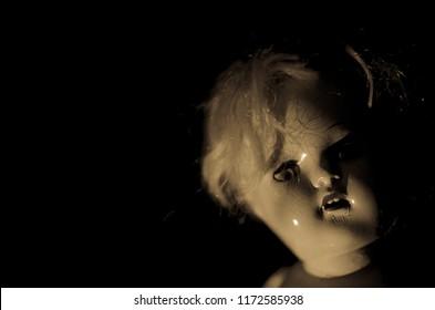 creepy doll smile in the dark in high contrast