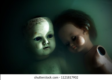Creepy dolls in dark dirty water