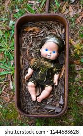 Creepy Grungy Old Baby Doll Laying in a Rusted Metal Wagon