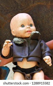 Creepy Grungy Old Baby Doll wearing a Leather Jacket