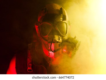 A creepy guy with post apocalyptic vibes wearing a gas mask in a smoke or fog cloud that's colored bright yellow while being lit with a red light from other side.