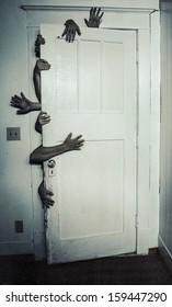 Creepy image of multiple hands opening a door