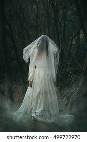 Creepy lone bride in misty woods . Halloween conceptual