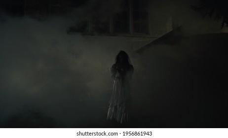 Creepy lone bride near misty medieval castle