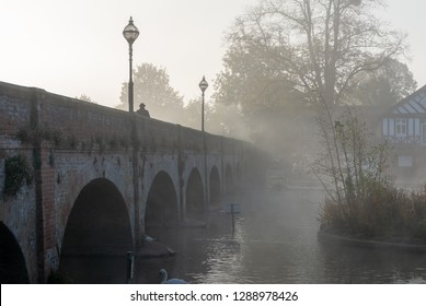 creepy looking man in trilby hat walks across misty arched bridge in Victorian England