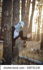 Creepy man in a suit and a rubber bird mask, standing in the sunset forest, behind the tree, waving to the camera