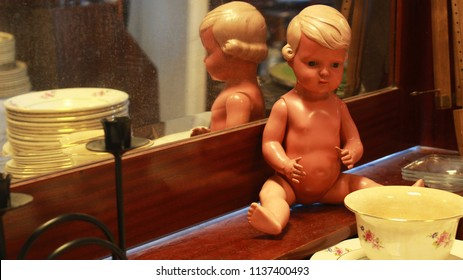 A creepy, naked, retro doll sitting naked with objects piled all around at a second-hand/antique store.