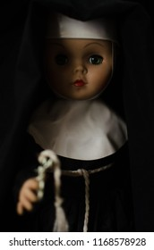creepy nun doll in the dark in selective focus