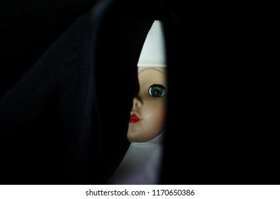 creepy nun doll hide in the dark and looking through in high contrast concept